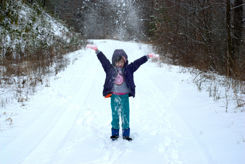 Girl tossing snow in the air