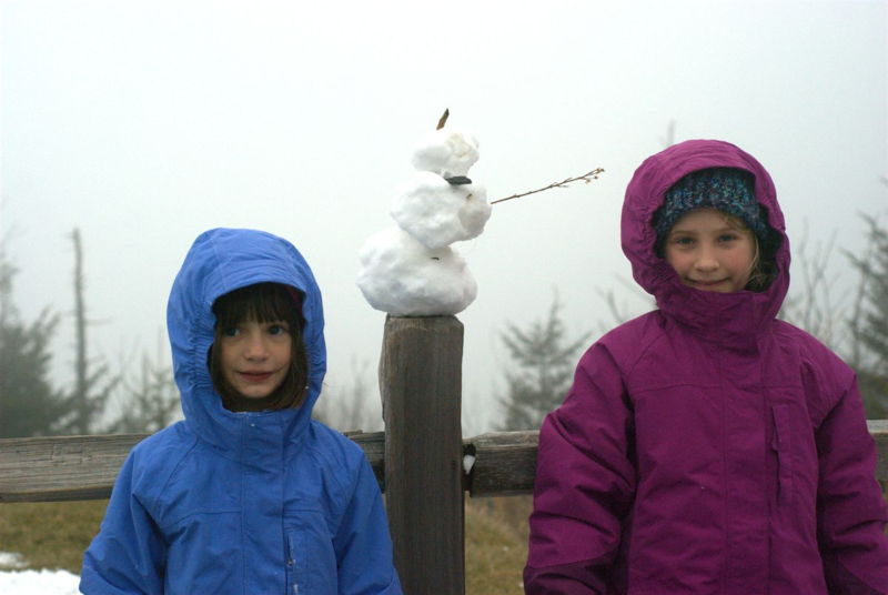 Two girls with  a tiny snowman
